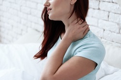 A woman sits at home and holds herself by the neck from severe pain. Woman doing neck massage at home.