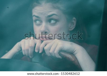 A woman sits behind the wheel of a car and looks aside a cropped look puzzled look