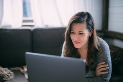 A woman sits in the living room with a laptop, looks at the screen, takes notes, learns a foreign language, reads an online training course, education on the Internet, consults with a client on video
