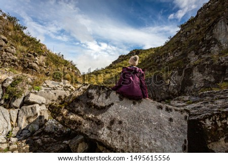 A woman sits on an ancient rock exposed and full of fossils from the sea.  The elevation of the land now over 1200 metres above sea level, located in Snowy Mountains Kosciuszko National Park #1495615556