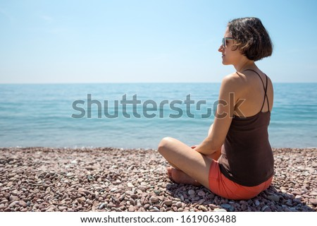 A woman sits on the seashore and looks into the distance. Slender girl looks at the sea. The brunette is sitting on the beach.
