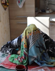 a woman sits over a table with a towel over her head