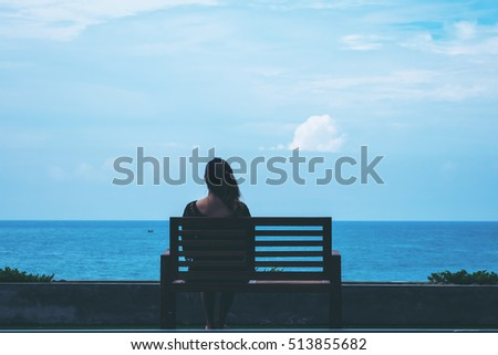 A woman sitting alone on a chair in front of the sea with feeling lonely