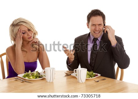 a woman sitting and being frustrated with her man because he is on the phone while they are having a nice dinner.  He is ignoring her.