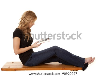 A woman sitting and relaxing on a bench reading a book