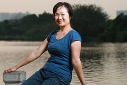 A woman sitting by a lake at sunset, looking at the camera and smiling