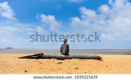 A woman sitting calmly on a old palm tree trunk is yearningly looking at the ocean #1039225639