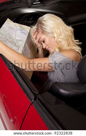 A woman sitting in her car with her hand on her head holding on to a road map.