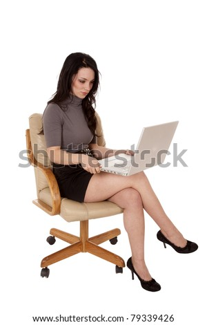 A woman sitting in her chair working on her laptop with a happy expression on her face.