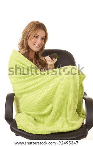 A woman sitting in her chair wrapped up in her lime green blanket with  a tv remote in her hands.