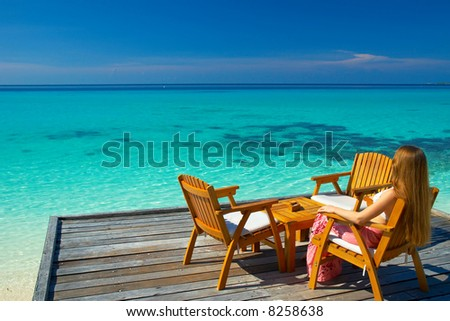 A woman sitting in the chair looking at the dreamy view on the horizon