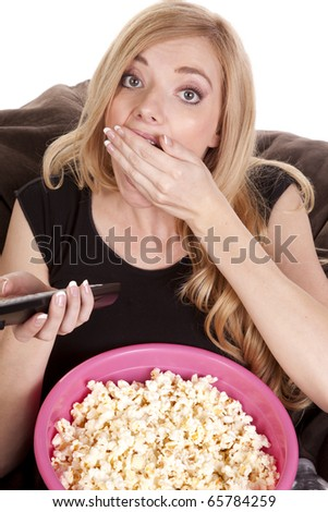 a woman sitting on a bean bag while she is enjoying her popcorn while she is watching tv