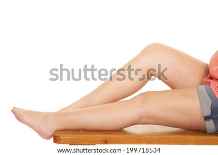 A woman sitting on a bench showing her legs.