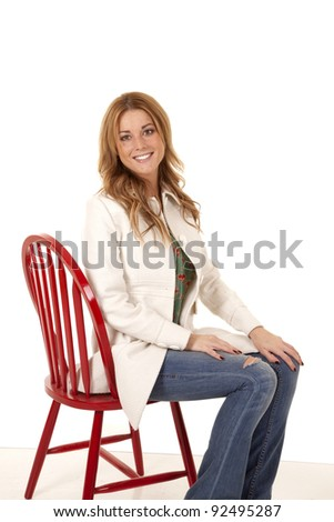 A woman sitting on a chair while wearing her white coat with a smile on her face.