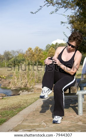 A woman sitting on a park bench grasping her knee as if injured.