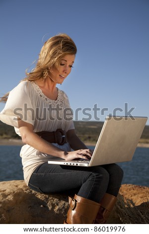 A woman sitting on a rock in her nice clothes working on her computer in the outdoors.