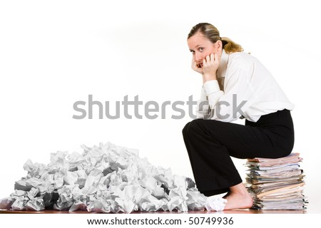 A woman sitting on a stack of files next to crumpled paper.