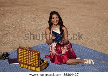 A woman sitting on her blanket at the beach with her picnic basket and she is reading a book.