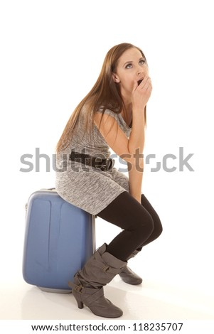 a woman sitting on her suitcase bored with what is going on.