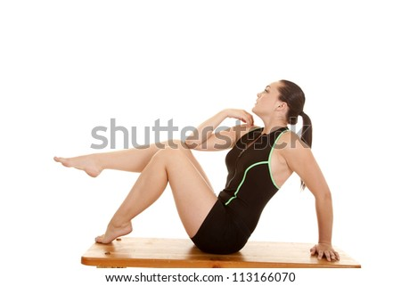 A woman sitting on the bench in her workout clothes with one leg up in the air.