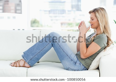 A woman sitting sideways on the couch, a cup raised up to her nose, and her eyes closed.