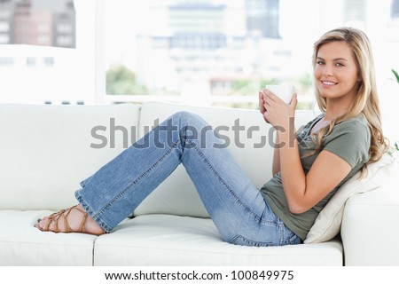 A woman sitting sideways on the couch, while looking forward and smiling with a mug in her hands.