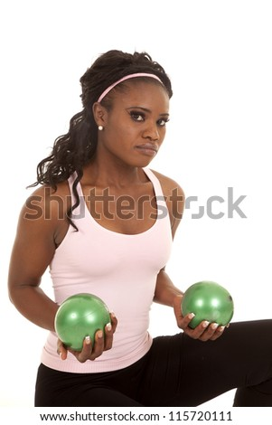 A woman sitting with a serious expression on her face holding on to green weighted balls.