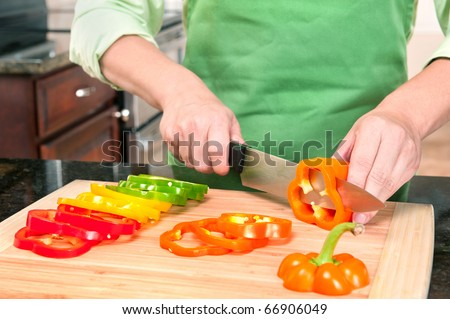 A woman slicing bell peppers prepares the vegetables as meal ingredients.