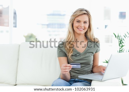 A woman smiling and looking in front of her uses her laptop as she holds her credit card.