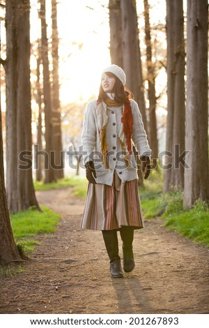 A Woman Smiling And Walking While Looking At Autumn Leaves - stock photo