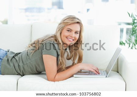 A woman smiling as she uses her laptop, while lying across the couch, and looking forward.