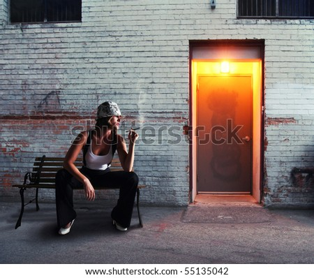 a woman smoking a cigar in an alley