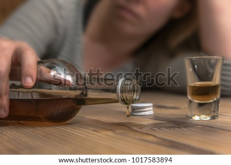 A woman (25-30) spills alcohol from an upturned bottle of brandy at the table. Concept: alcohol abuse or drinking