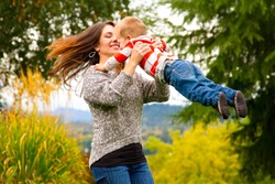 A woman spins her child around while holding him in the air in this joyous happy moment.