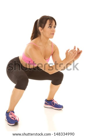 A woman squating and showing her strength by holding this pose