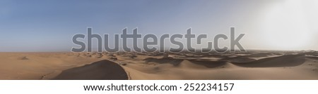A woman standing alone looking down from the edge of a big sand dune in the Sahara desert in Erg Chegaga in Morocco in the spring during a hot sunny day.