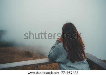 A woman standing alone on balcony looking at white foggy and mountains background #771989422