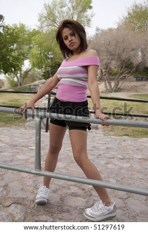 A woman standing and posing on a bridge in the great outdoors with trees, rocks, and grass with a serious expression on her face.