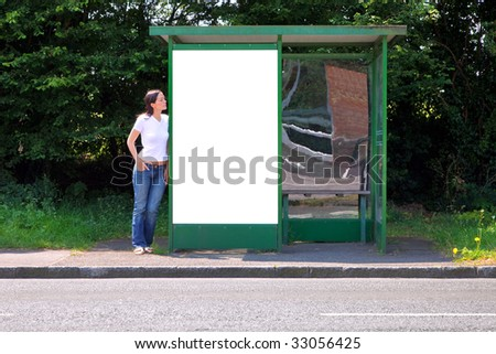 A woman standing at a rural bus stop leaning on a shelter with a blank billboard, clipping path included for you to add your own message in the space.