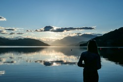 A woman standing at the shore of Millstaetter lake during the sunset. High Alps around. The sun sets behind thick clouds. Calm surface of the lake reflects the orange sky and the mountains. Day end