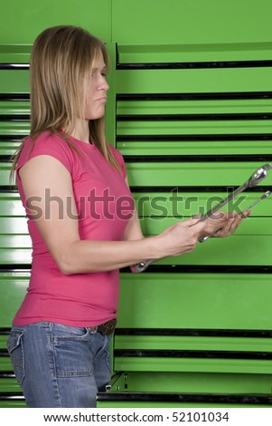 A woman standing by a green toolbox trying to decide which tool would be right for the job. - stock photo