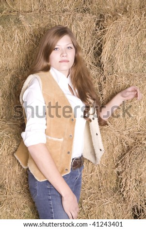 A woman standing by a pile of hay with a brown vest with fur with a serious look on her face.