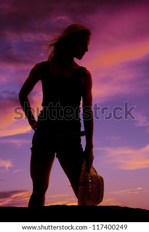 A woman standing in a beautiful sunset holding on to her hat.