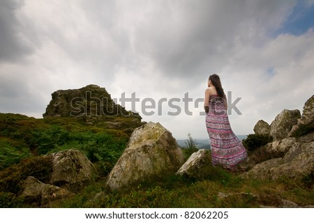 a woman standing in a dress looking up at a rocky mountain