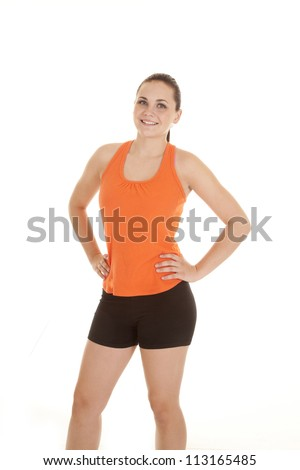 A woman standing in her orange and black workout clothes, with a smile on her face.