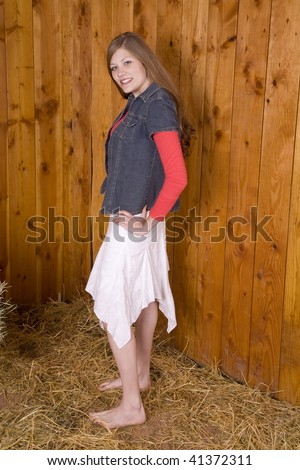 A woman standing next to a wood wall in the hay with her bare feet in a white skirt with a small smile,