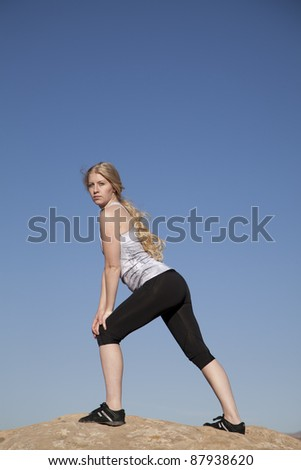 A woman standing on a rock stretching out her legs.