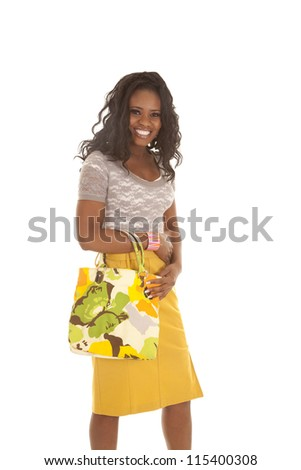 a woman standing with a smile on her face holding on to her colorful purse.