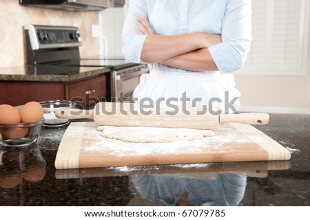 A woman standing with her arms crossed contemplates the baking she is about to conduct.