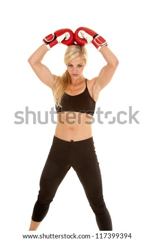A woman standing with her boxing gloves on her head.
